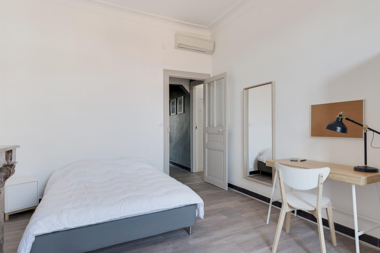 grande chambre avec lit double dans une colocation meublée