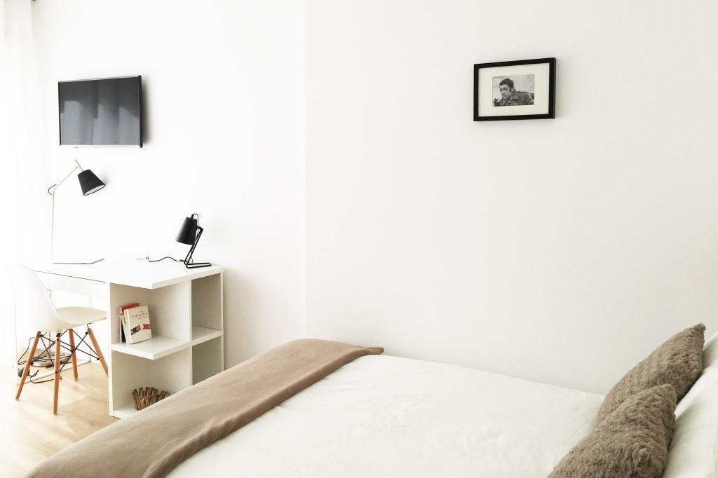 grand lit dans un studio meublé moderne